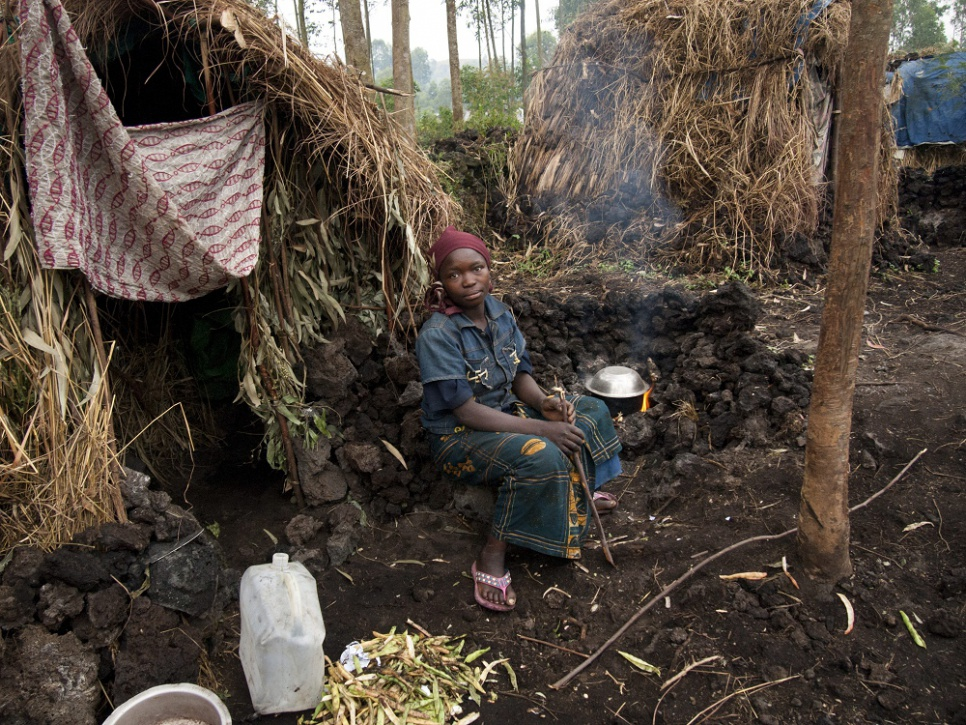 A young displaced Congolese woman cooks dinner in a camp in eastern Democratic Republic of the Congo. Displacement has become a way of life for many in the region, and displaced women are at great risk of abuse, including rape.