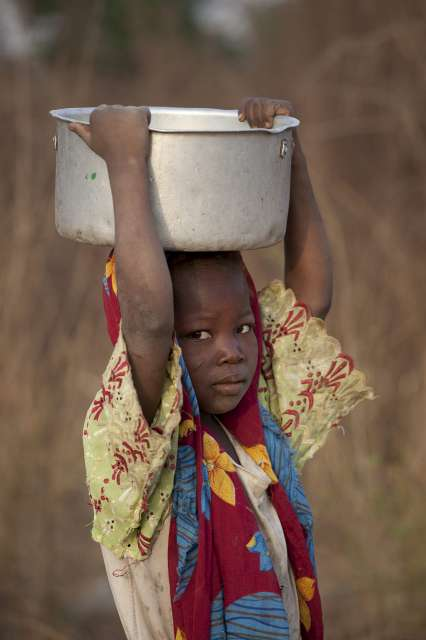 A young refugee girl carries water in Chad's Nya-Pendé province.