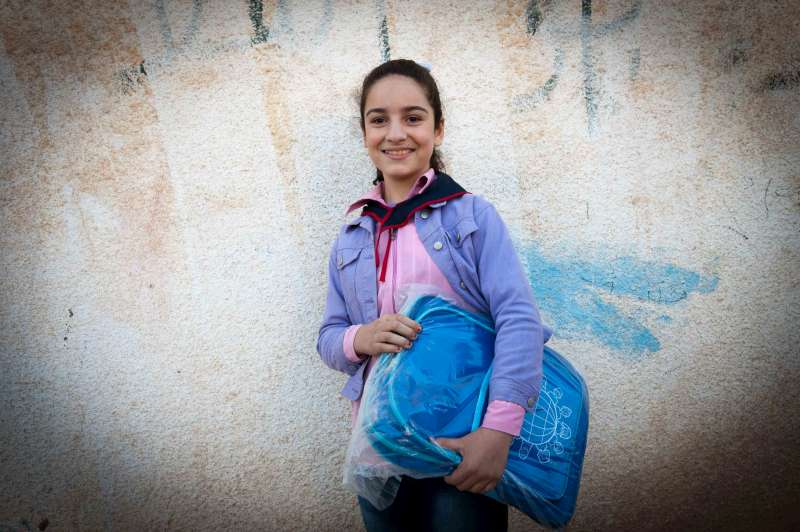 This girl, who has been displaced within Syria, happily holds a school bag she has been given in Hassakeh. About half of the 1 million Syrians who have fled their country over the past two years are children, including 236,000 girls.