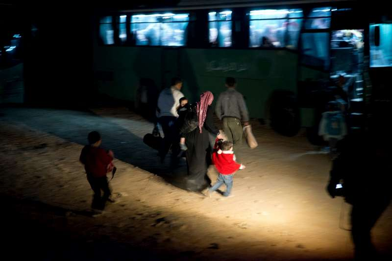 A family of Syrian refugees heads to a waiting bus for transport to Za'atri refugee camp.