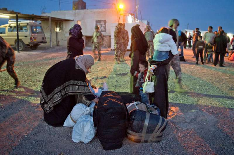 An elderly mother and her adult daughters, with their children, take a breather at a processing point near the Jaber border crossing. Her daughter's husbands took them to the border and then returned to Syria.