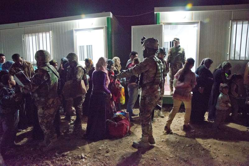 Members of the Jordanian military organize Syrian refugee families as they wait to register at an undisclosed location along the border.