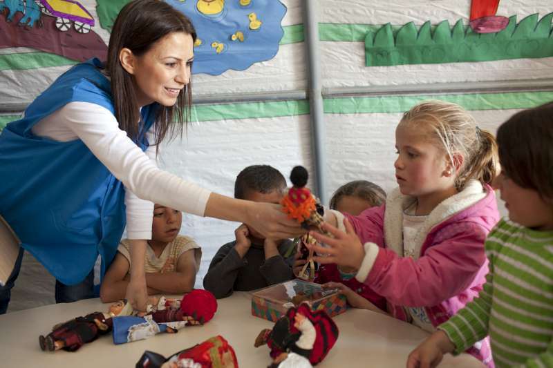 A UNHCR staff member gives a doll to a rosy-cheeked, four-year-old […]