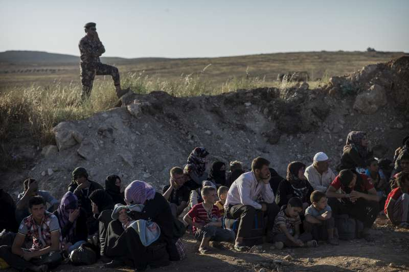 Syrians are instructed to wait behind a slope created by the Jordanian army to protect new arrivals.