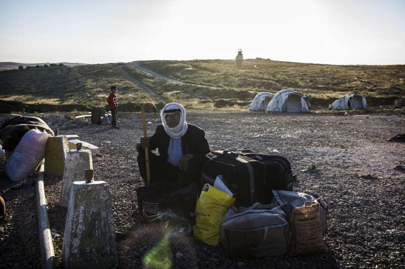A Syrian refugee stops and rests with his belongings at the end of his journey from Syria.  He has just crossed the border, which can be seen behind him.