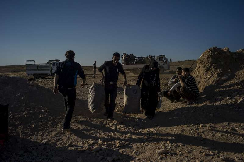 Syrians fleeing the war carry their belongings across the border from Syria to Jordan.