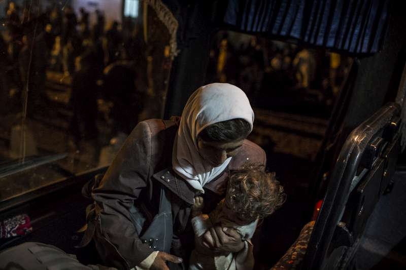 A newly arrived Syrian refugee woman carries her child as she boards the bus that will take her to Za'atri.