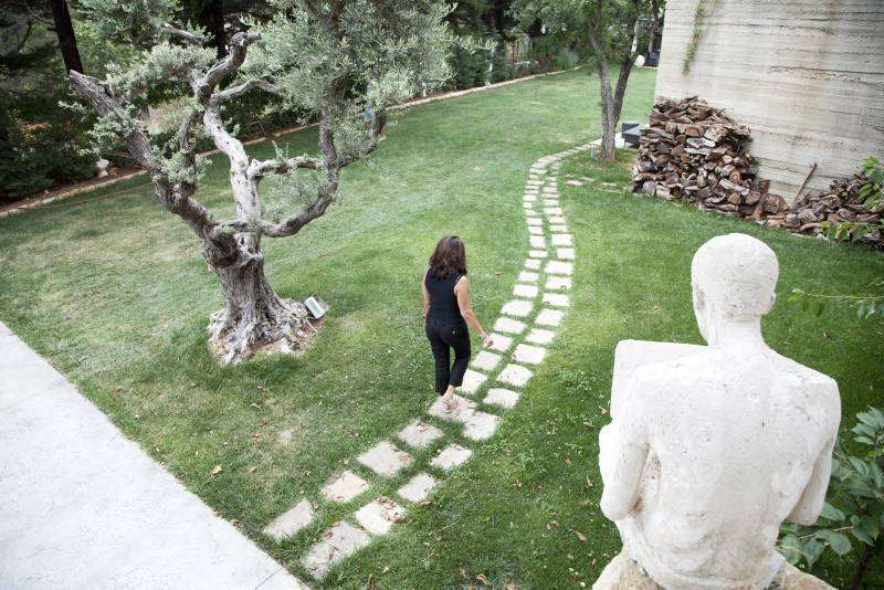 Raghad Mardini, founder of the Art Residence Aley, walks through the grounds of the retreat. She renovated an old coach house to create studio space for Syrian artists.