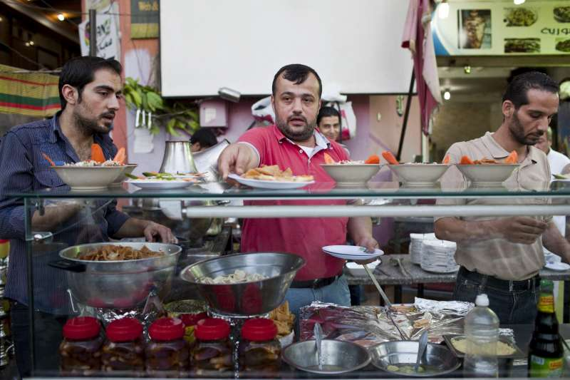 "Day 6: Syrian chef, Galal (centre), prepares the evening iftar meal during Ramadan at the busy Bab Elhara Restaurant in Cairo. ""I've worked in several restaurants in Syria and Saudi Arabia and I love cooking,"" he reveals, adding that his father cooked for an ambassador in Syria and taught 35-year-old Galal how to cook. ""The first dish he taught me to cook is kibbeh [a Levantine dish made from bulgar, minced onions and ground meat], which is important not only during Ramadan - it's the jewel of any dinner."" But Galal lost his job a year ago when things got worse in Damascus and restaurants began shutting down. He fled to Egypt a month ago with his wife and two children. The thing he misses most about Ramadan in Syria is getting together with his whole family. ""I was away from Syria for eight years of my own free will in Saudi Arabia and Qatar, but now I'm away forcibly. As soon as things calm down, I will go back home."""