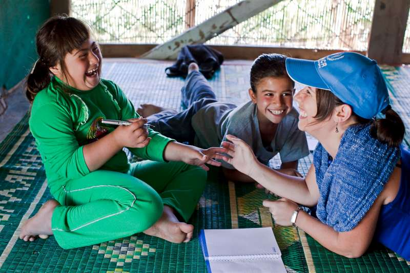 Aya and Labiba share a light moment with UNHCR staff member Roberta Russo in their family home.