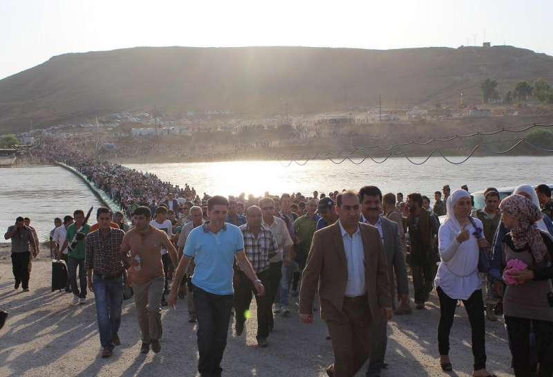 Thousands of Syrians streamed across a bridge over the Tigris […]