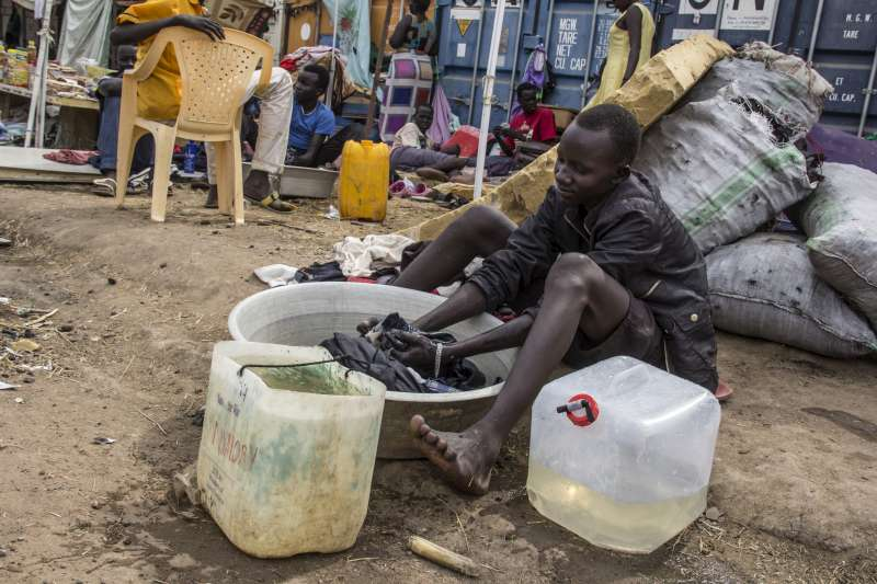 A teenager displaced by recent violence washes clothes in a basin […]