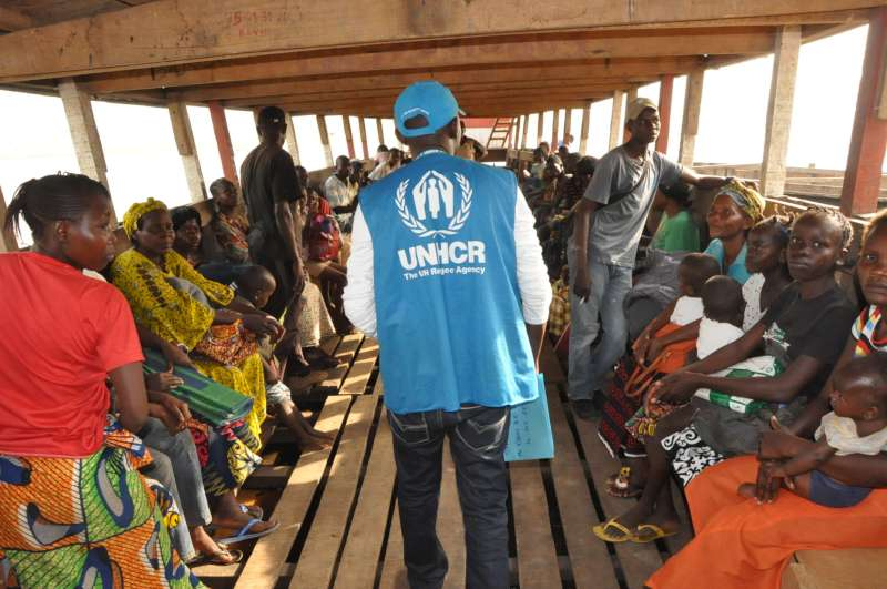 A UNHCR staff member, Baudelaire, makes a final roll-call before departure.