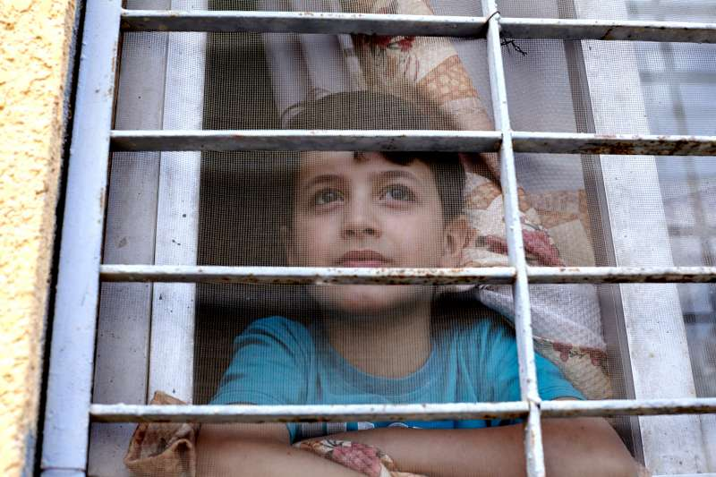 Syrian refugee, Mahmoud, aged nine, looks out of the window of […]