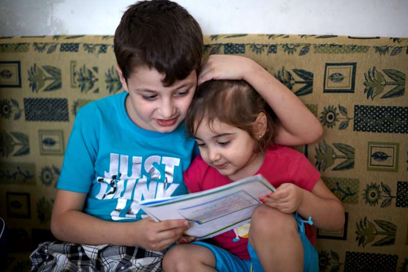 Mahmoud reads to his two-and-a-half-year old sister, Bisam, in their home in the Beit Al Aila neighbourhood in the 6th of October City.