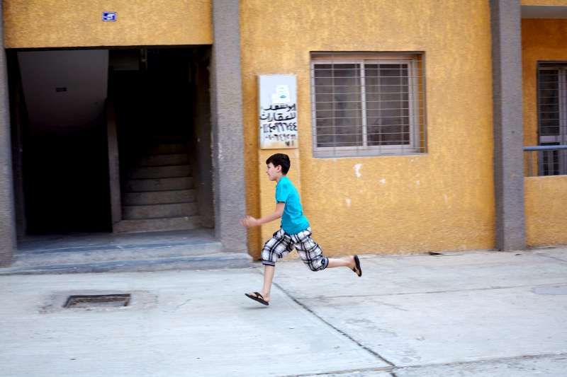 Mahmoud runs to visit a neighbor in the drab housing estate where his family's apartment was located.