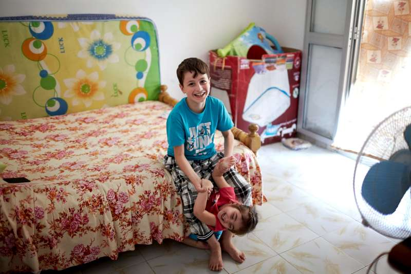 Mahmoud plays with his sister in their apartment in the Beit Al Aila neighbourhood. His father says that his son used to play with local children, but they turned against him.
