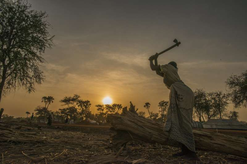A woman chops firewood in South Sudan's Doro Camp. Wood for cooking and heating is in very short supply in the area, but going out to look for firewood can be dangerous for women and girls who are vulnerable to attack.