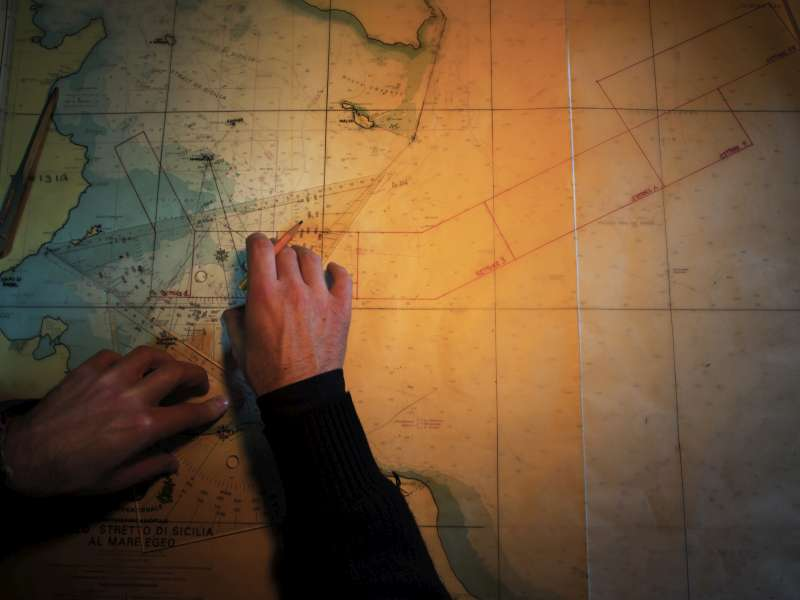 A crew member of the San Giusto charts the most common routes used by people smugglers to cross the Mediterranean from North Africa.