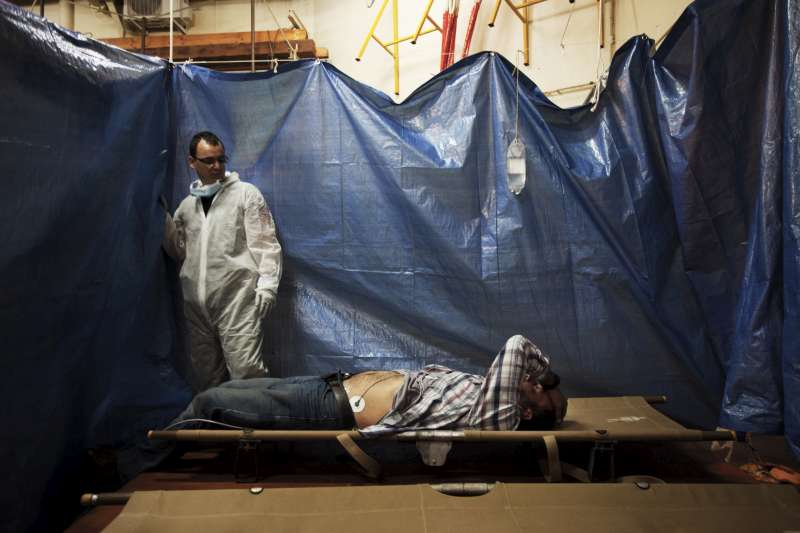 A newly arrived Syrian refugee awaits emergency medical assistance in a makeshift treatment space in the hold of the San Giusto.