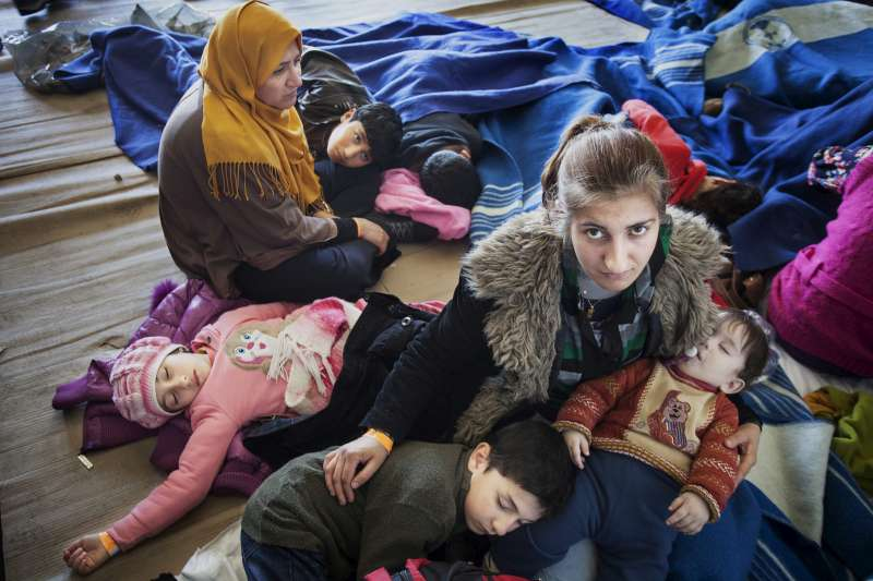 A Syrian mother sits on a deck of the Italian vessel, Verga, with her young children. They were rescued from a fishing boat carrying 219 people while attempting to cross the Mediterranean Sea from Libya.