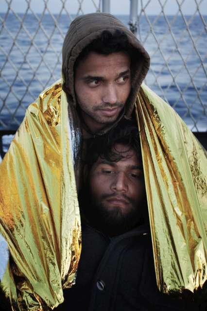 Two young men share a thermal blanket after being rescued trying to cross the Mediterranean Sea from Libya.