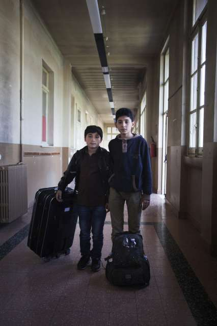 Two boys who were rescued at sea stand in the hallway of a former school that is being used as a reception centre for newly arrived Syrian refugees in Italy. Families usually spend a few days in the centre.