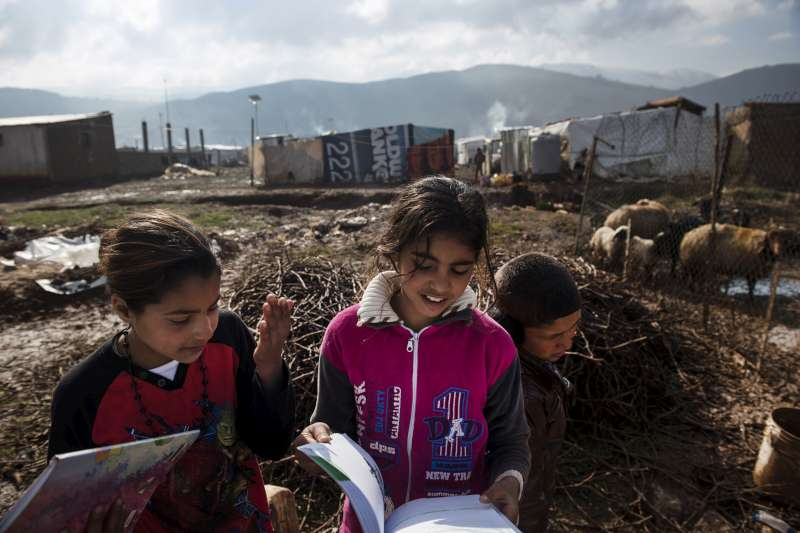 Sharifa (left), 12, from the Syrian city of Homs, studies by […]