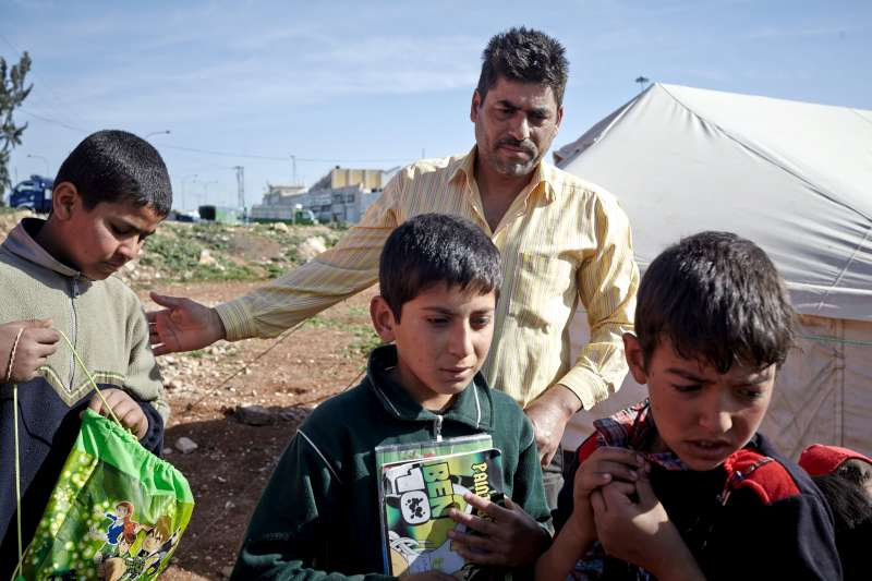 Jamal ushers students into the school, which is no more than a tent with a carpet and a whiteboard inside. It is located in a tented settlement in Kherbet Al-Souk on the outskirts of Amman, Jordan.