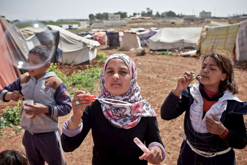 Three Syrian refugees blow bubbles in a break from class at the settlement in Kherbet Al-Souk.