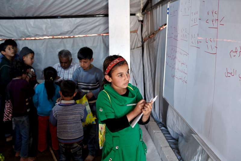 Ten-year-old Syrian refugee, Asmaa (in green), works on a maths problem as her teacher, Akram, speaks in the background with other students at the refugee school in Kherbet Al-Souk.