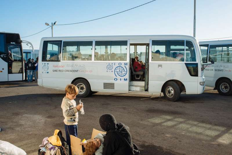 A woman and her children wait to board the International Organization for Migration bus that will take them to their new shelter in Azraq camp.