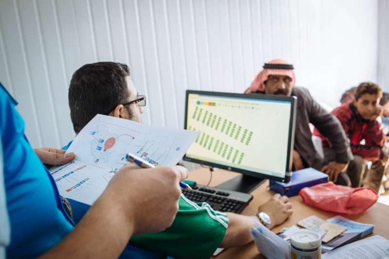 Abu Saleh sits with UNHCR staff as they use a computer to assign him a shelter in the camp.