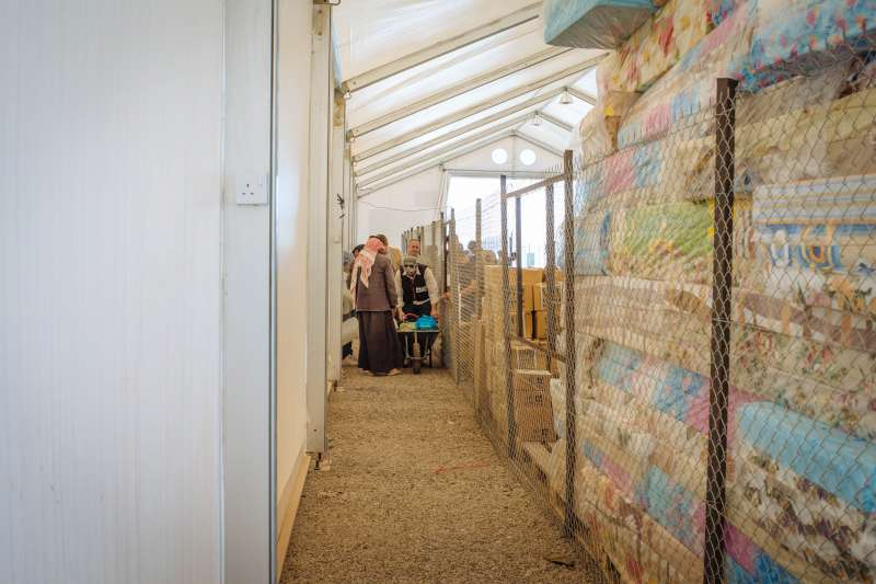 Abu Saleh visits this Norwegian Refugee Council warehouse to get basic aid items for his family. The store is piled high with mattresses and other relief supplies.