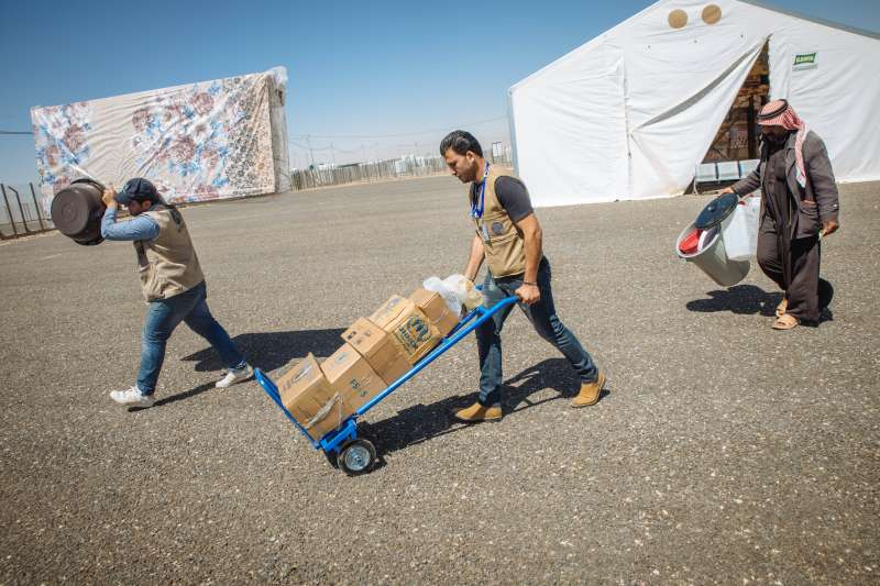 Staff from the French aid agency, ACTED, help Abu Saleh carry the food packages and other essential items that the family will need as they begin a new life at Azraq camp.
