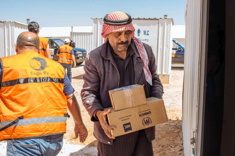 "Abu Saleh carries an aid pack into his shelter. ""I am very grateful for the kindness and support we have received,"" he says. ""The shelter is much better than we had anticipated."""