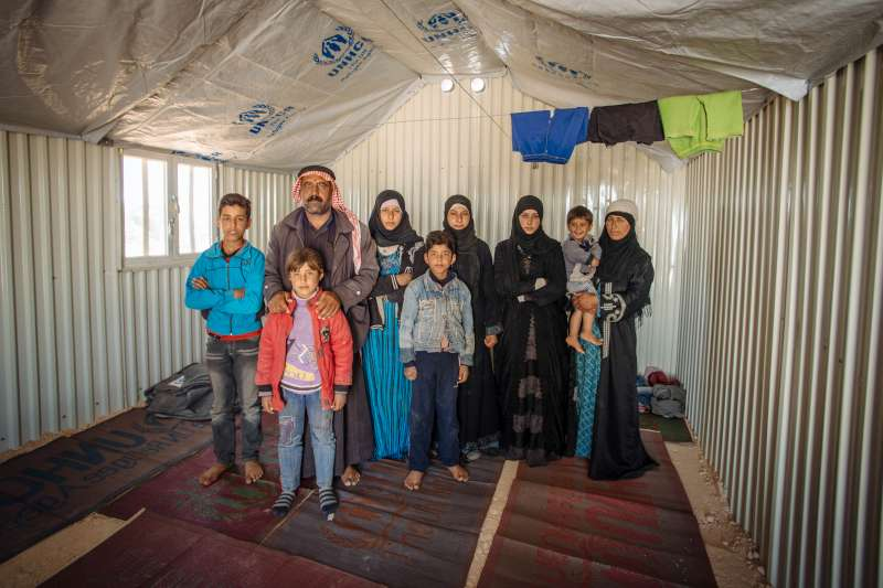 Abu Saleh, his wife, Dalah, and their seven children pose in their spartan new shelter. It will soon become more homely. It's a far cry from their home in northern Syria, but at least they are safe.
