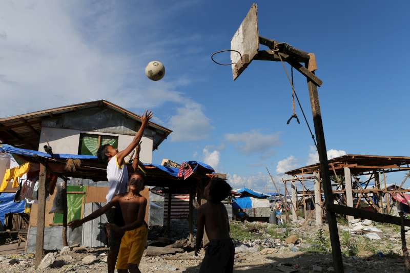 Children play basketball in storm-damaged Anibong, near the city […]