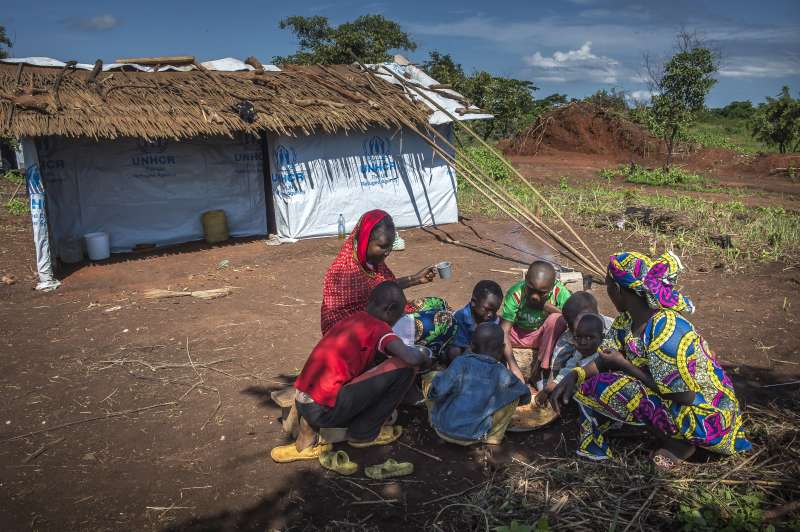 Ramatou and her children eat breakfast at the makeshift shelter of relatives in Mbile Refugee Camp, the day after her reunion with her two sons Ibrahim and Moussa.