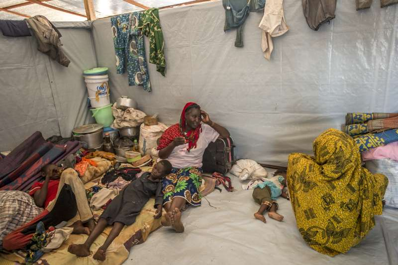Ramatou rests in her temporary shelter in Mbile camp with some of her children, including Ibrahim (left), who seems to feel quite at home. She has a smile on her face. For the first time in four month, she slept well.