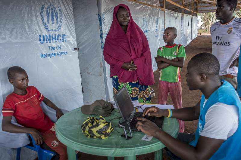 A UNHCR worker registers Ibrahim and Moussa on a computer. Their names will be included on their mother's ration card, alongside the names of eight siblings.