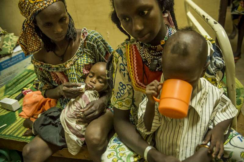 Two mothers nurse their malnourished children in Batouri Hospital's nutrition centre. UNHCR gives them advice on the care that is needed to restore their children to good health.