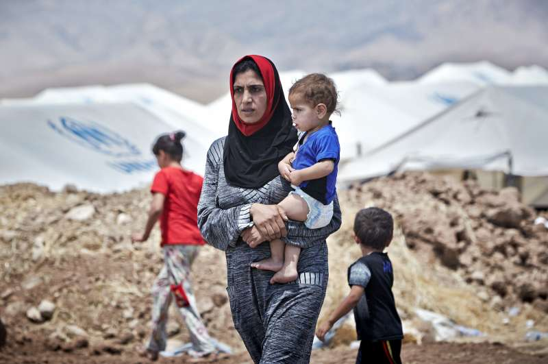An Iraqi woman from Mosul carries her son at the Garmava transit […]