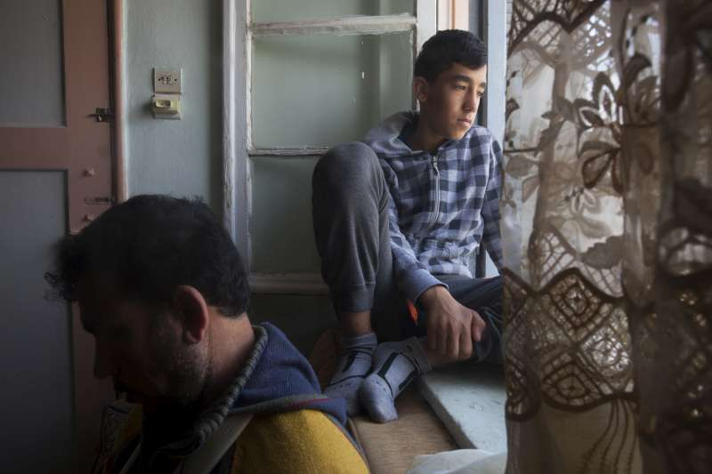 Malak, 13, looks out of the window next to his father in the […]