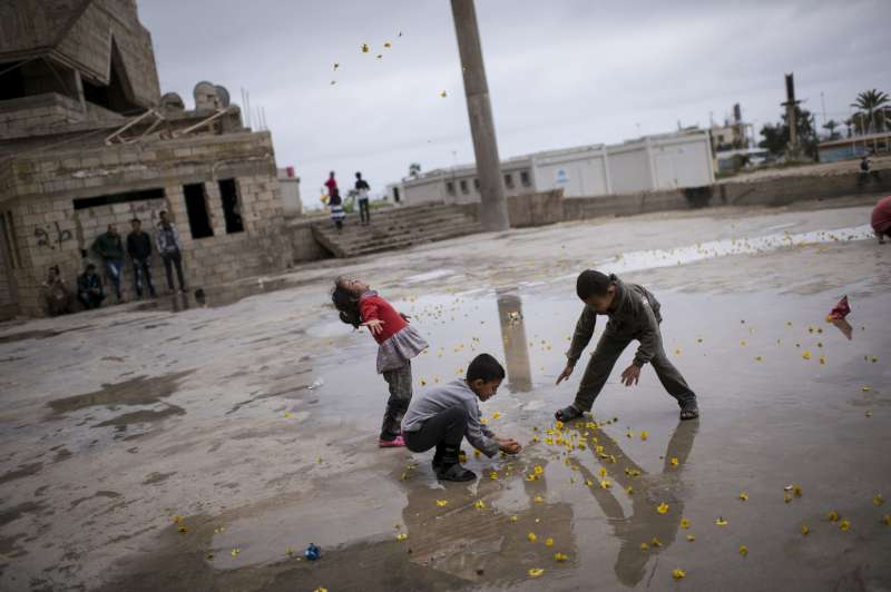 Lebanon/ Syrian refugees/ Saida: Syrian refugees play outside of the Ouzai collective shelter in Saida, Lebanon, March 4, 2014. Lebanon, a country of just over four million people, is preparing to officially register its one millionth Syrian refugee as the Syrian conflict reaches its third anniversary.  Fifty percent of the Syrian refugees are children, most of whom have been out of school for up to three years.  Lebanon's resources have been overburdened by the surge in population, and with no official refugee camps in the country, Syrians are forced to live in makeshift shelters across the country. UNHCR/Lynsey Addario/ March 2014