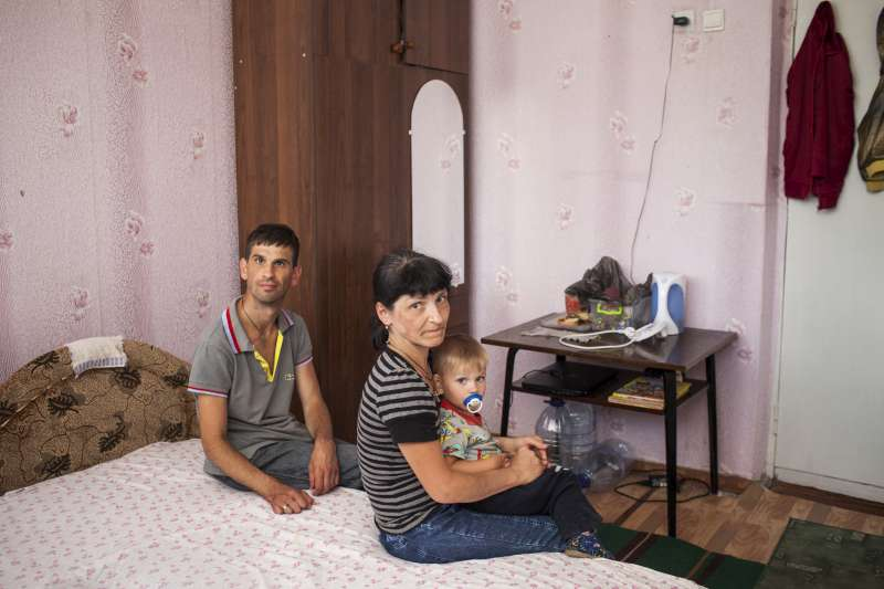 Viktoria and Aleksandr sit with 19-month-old Ivan in their room […]
