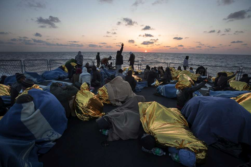 During one Mare Nostrum rescue operation, 220 people – from Nigeria, Pakistan, Nepal, Ethiopia, Sudan, Malaysia and Syria – huddle under blankets on the deck of an Italian Navy ship, waiting to be transferred to the mainland.