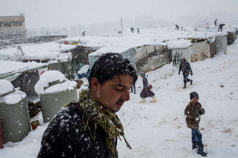 Syrian refugees move between shelters at an informal tented settlement […]