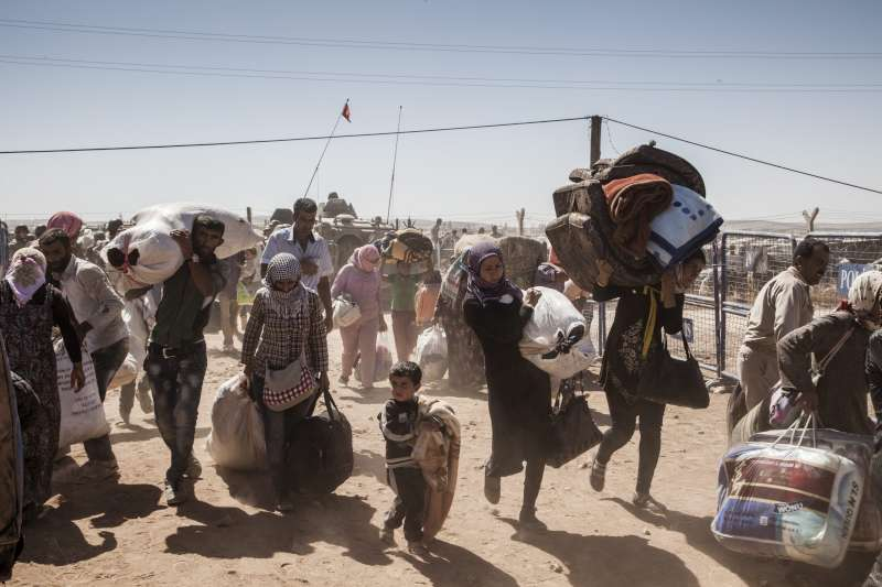 Syrian refugees cross over into the outskirts of Kobani, Turkey, […]