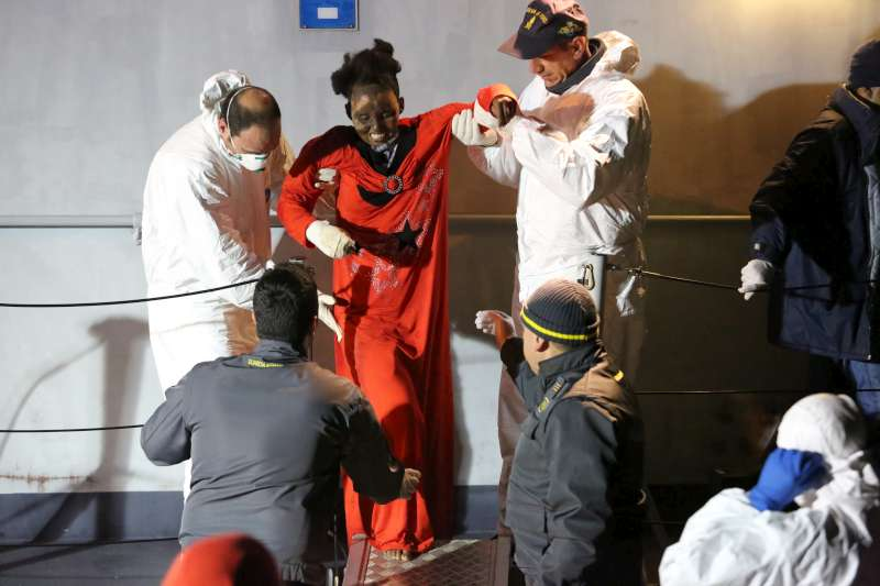 A woman with severe burns to her face is helped off of an Italian Coastguard vessel in Lampedusa. She was plucked from a dinghy in the Mediterranean and later taken by helicopter for treatment.